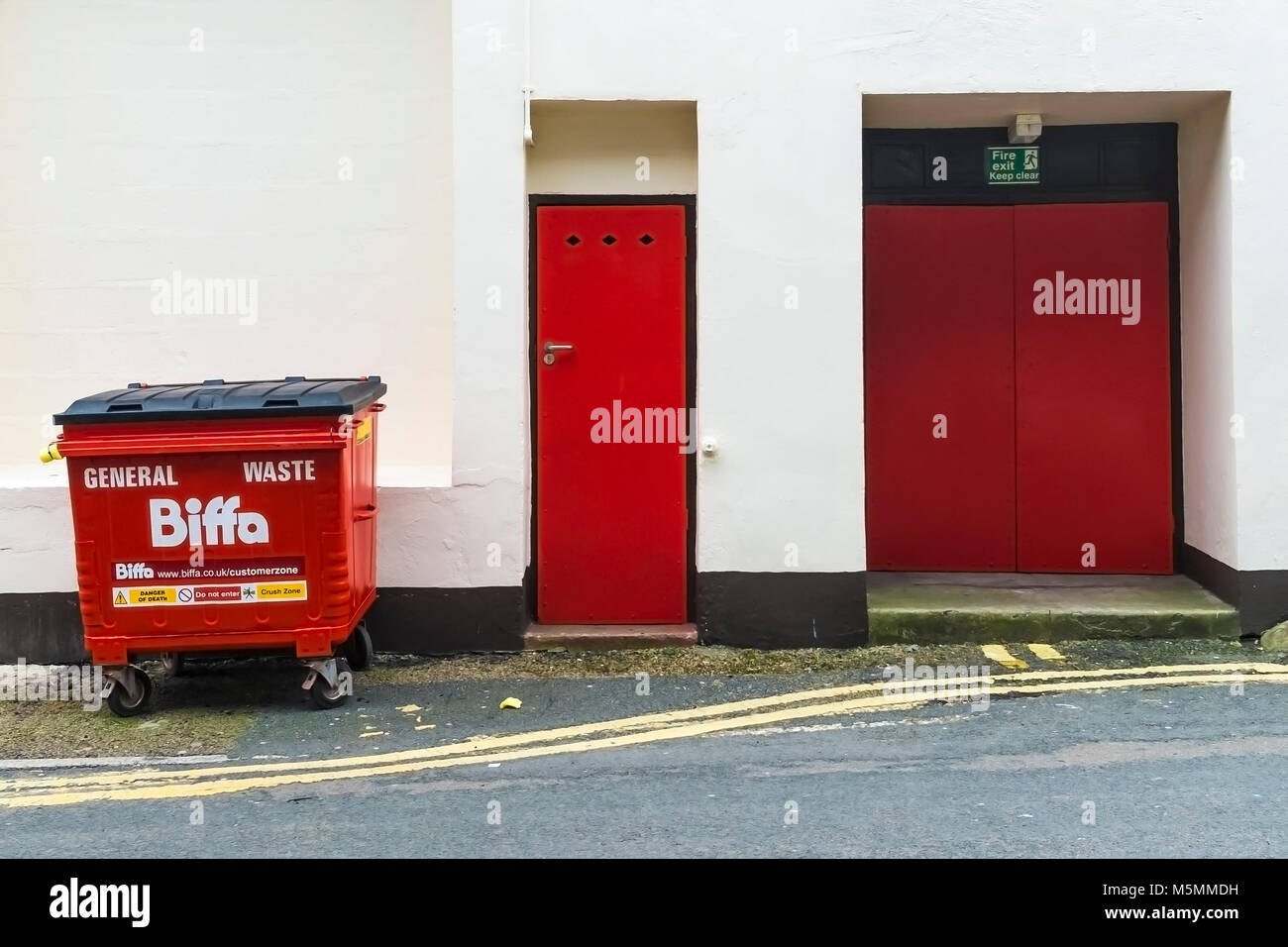 Two red doors and a red Biffa commercial waste bin. - Stock Image