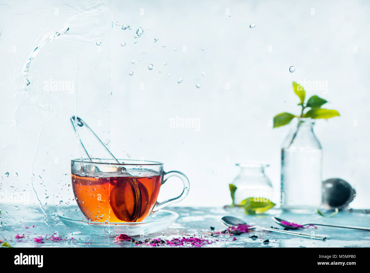 Cup of tea, transparent on a light background with glass bottles and green leaves. Spring still life with raindrops - Stock Image