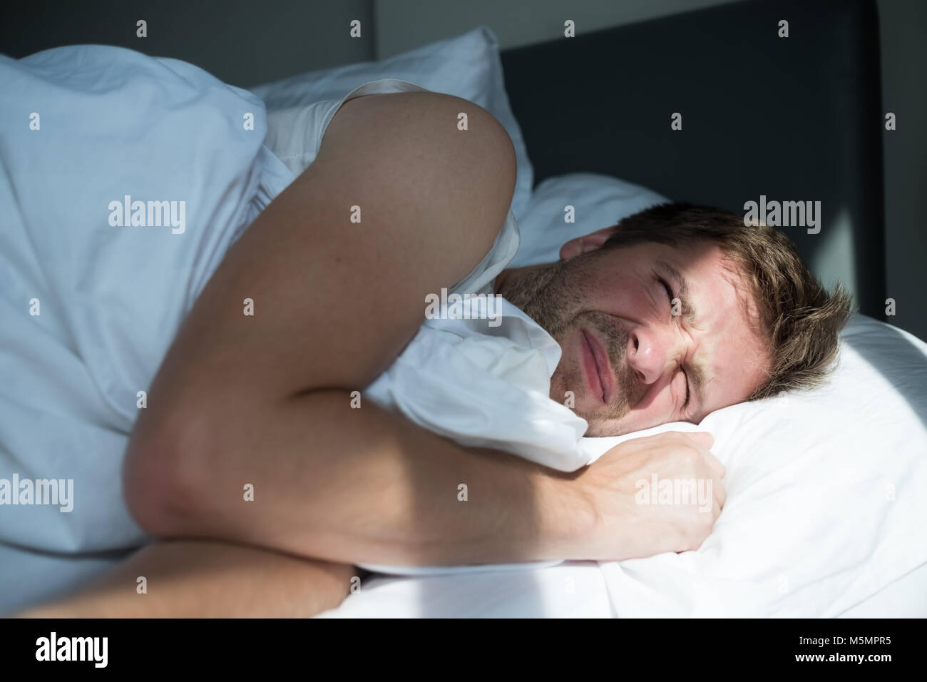 Caucasian mature man in white t-shirt does not want to get up in the morning - Stock Image