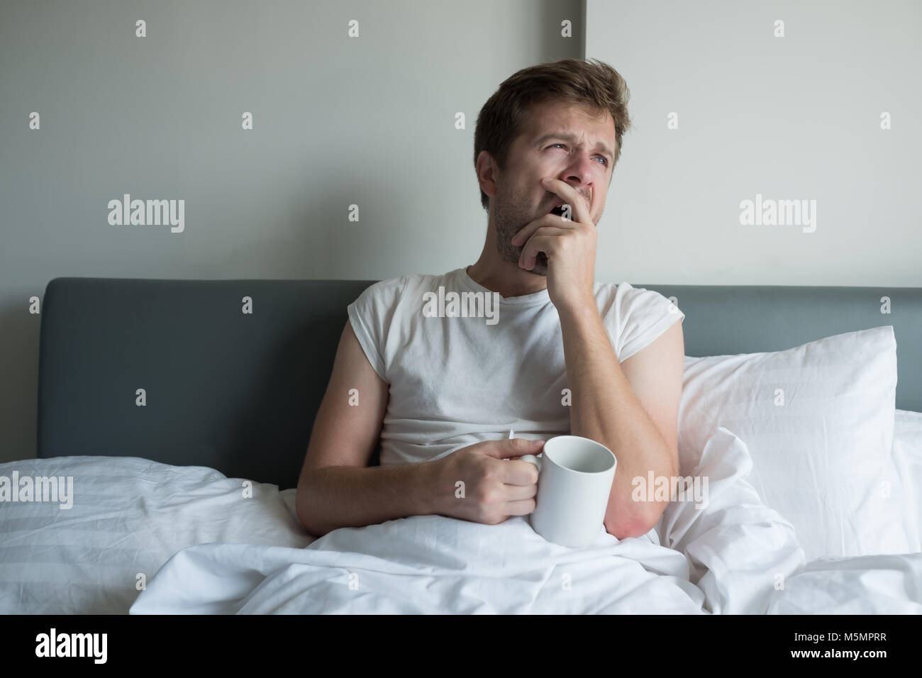 Young handsome man yawning and having morning coffee in bed - Stock Image