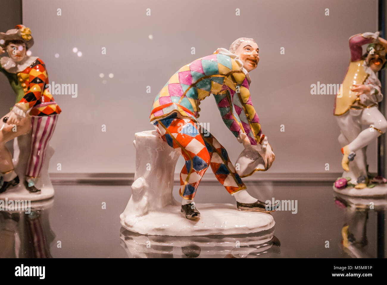 ceramic art figure scowling harlequin - Stock Image