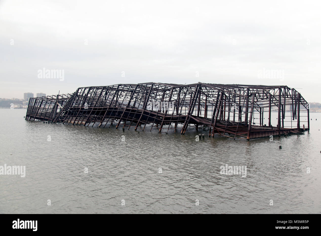 Abandoned metal built structure collapsed in the river - Stock Image