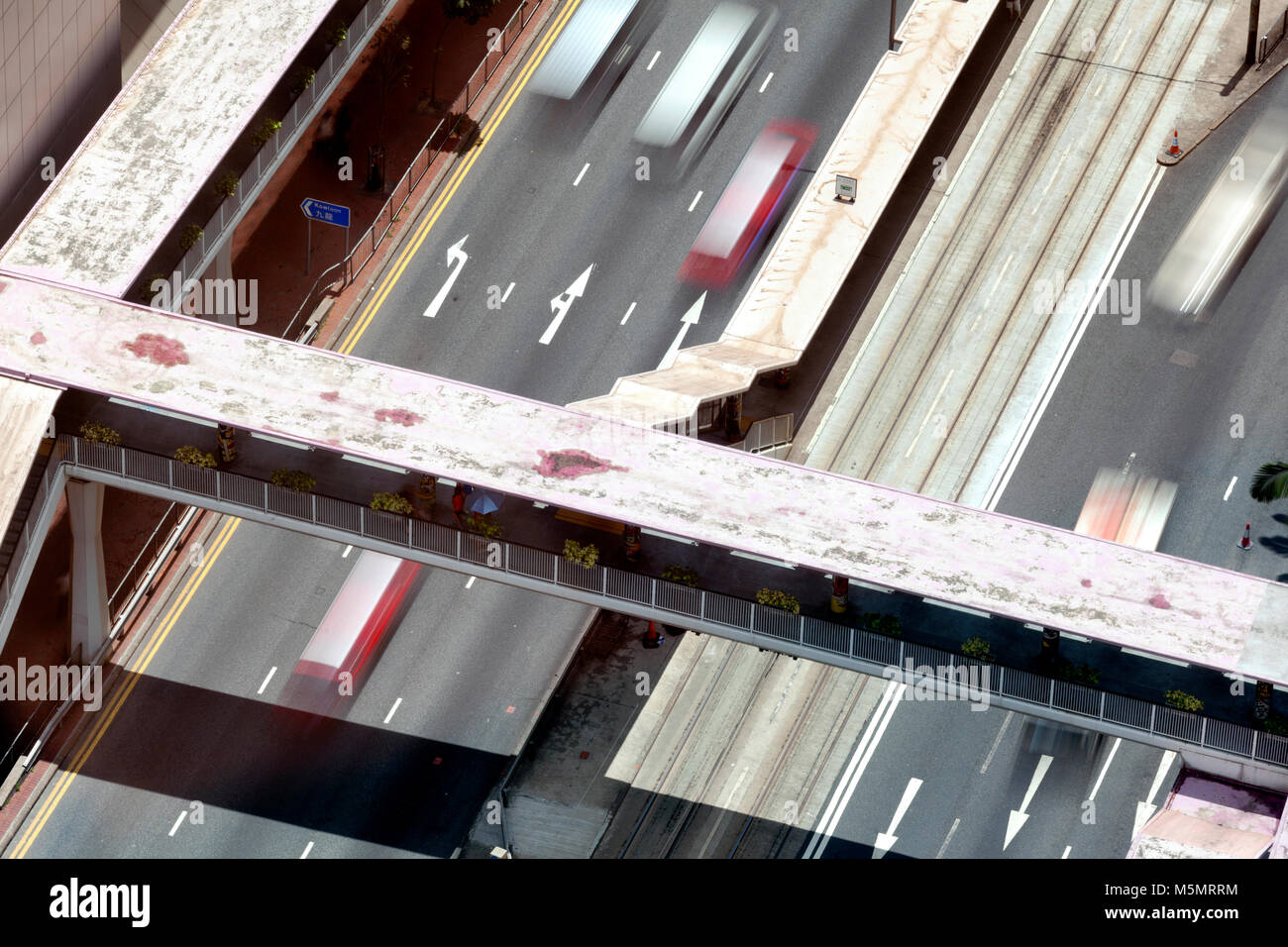 A bird eye view of an elevated tunnel over an highway and cars in motion in the city of Hong Kong, China - Stock Image