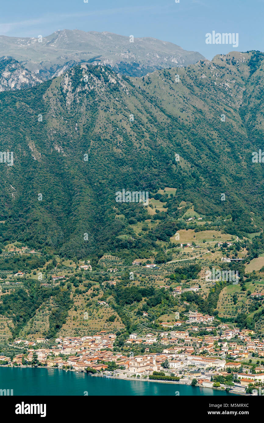 View of Sale Marasino on Lake Iseo in Northern Italy with small towns and mountains above it. - Stock Image