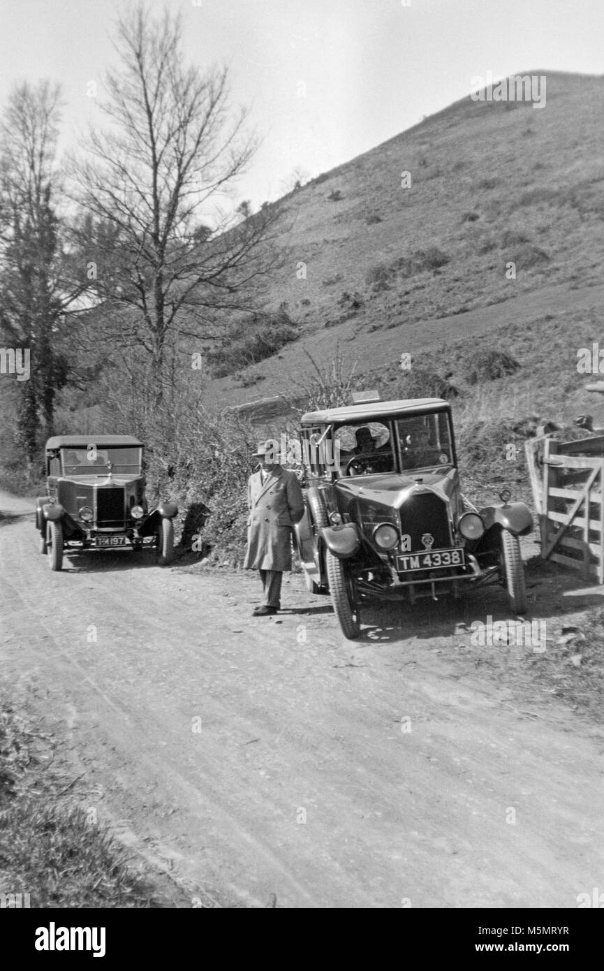 Contemporary black and white 1920s image of two vintage cars parked by the side of a small road in the British countryside. Stock Photo