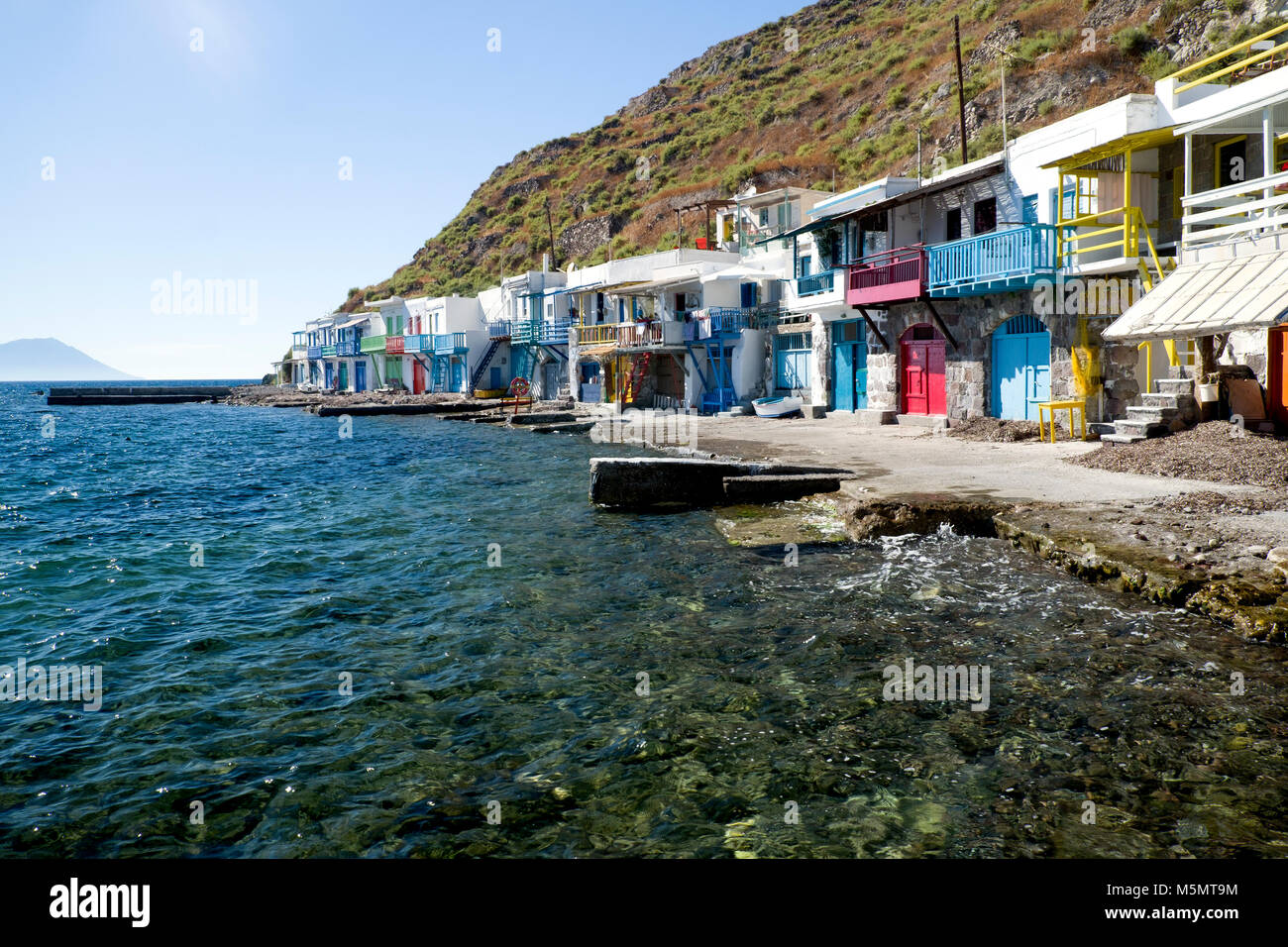 Brightly coloured fishermen's houses (syrmata) on the waterfront at Klima, Milos. Each property has a boat 'garage' - Stock Image