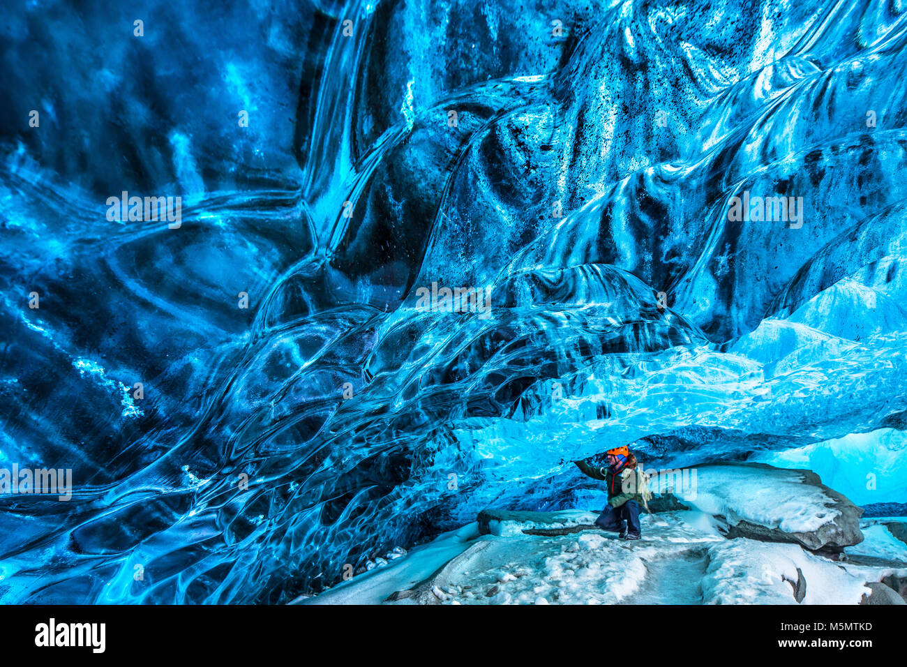 Tourist discovering the ice cave, active traveler man enjoying beauty of a glacial cave, extreme winter vacation, - Stock Image