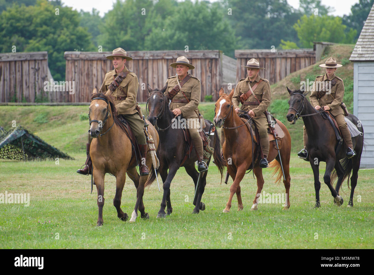 Reanactors dressed in period costume performing a horse riding display at Fort George National Historic Site, Niagara - Stock Image
