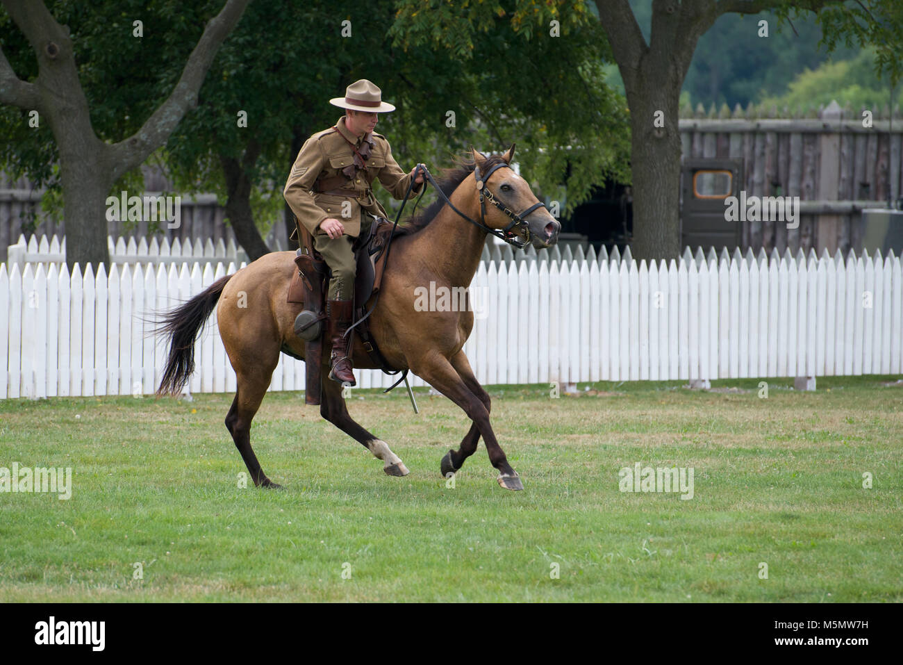 A reanactor dressed in period costume performing a horse riding display at Fort George National Historic Site, Niagara - Stock Image