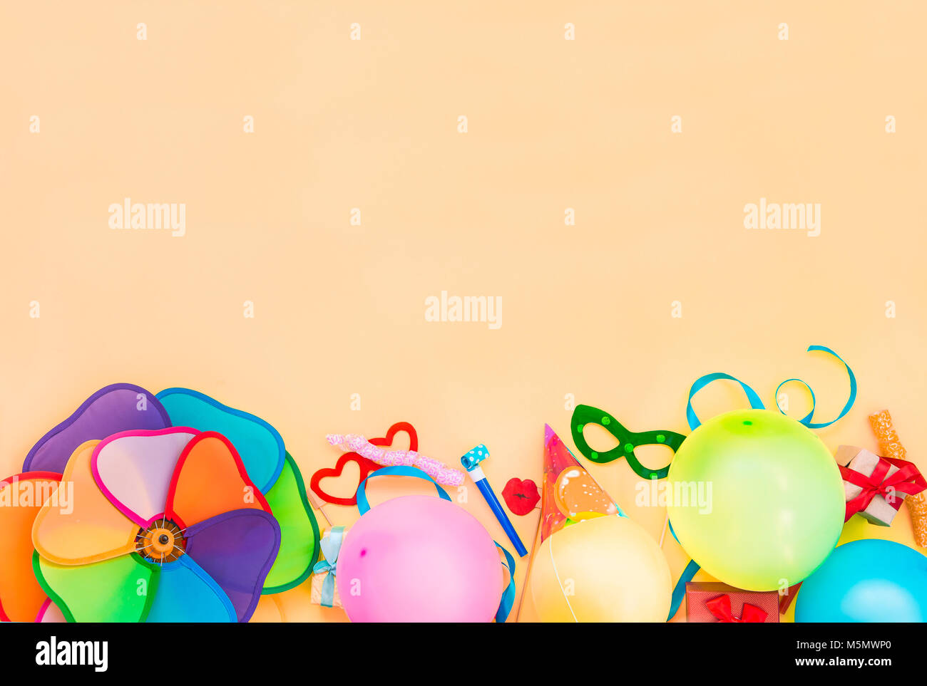 Top view bright party tools and decoration - baloons, funny carnival masks, festive tinsel on peach color background. - Stock Image