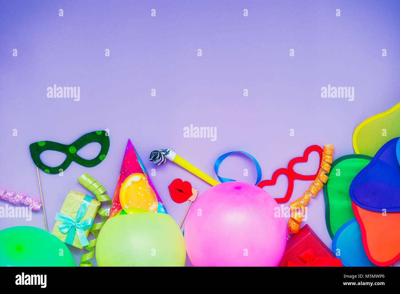 Top view bright party tools and decoration - baloons, funny carnival masks, festive tinsel on lilac background. - Stock Image