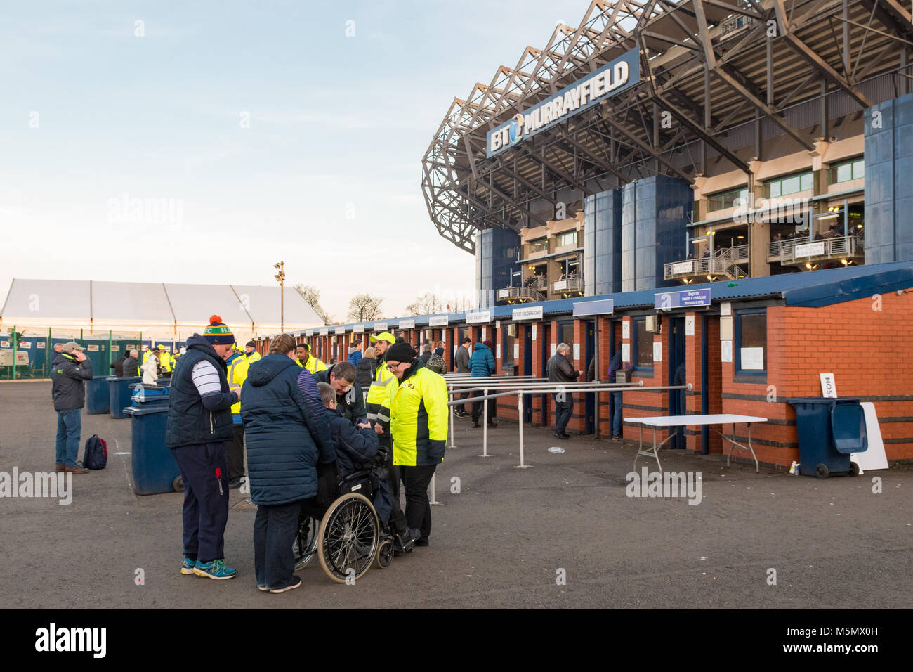 Disabled spectator in wheelchair outside BT Murrayfield Stadium for the England Scotland Six Nations Rugby game - Stock Image