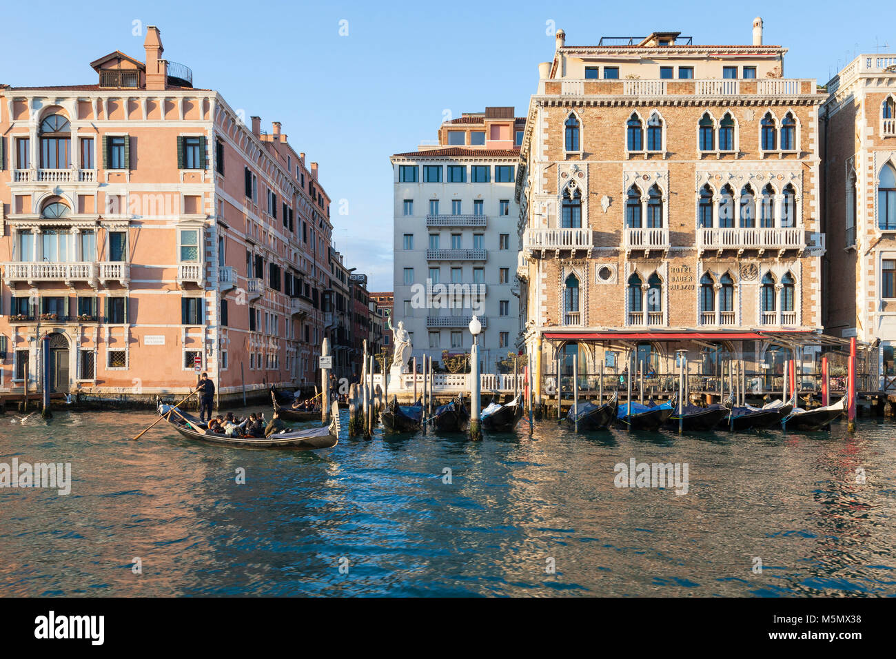 Tourists enjoying a gondola ride on the Grand Canal at sunset, Venice, Veneto, Italy passing the Hotel Bauer Palazzo - Stock Image