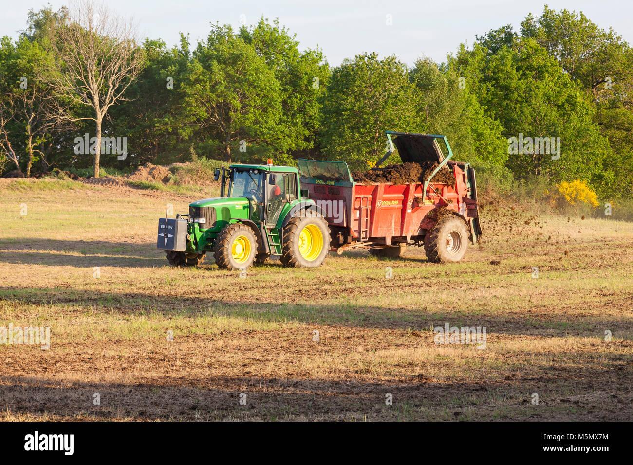 Farmer spreading organic fertiliser, fertilizer  or manure on a spring pasture using a Degullaume muck spreader - Stock Image