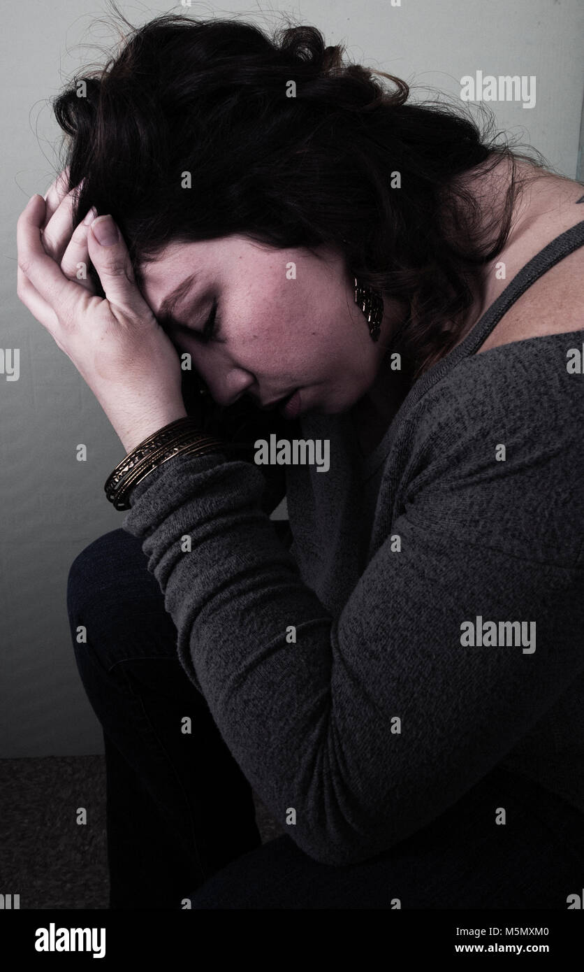 Young woman sitting with her hand to her face looking upset. - Stock Image