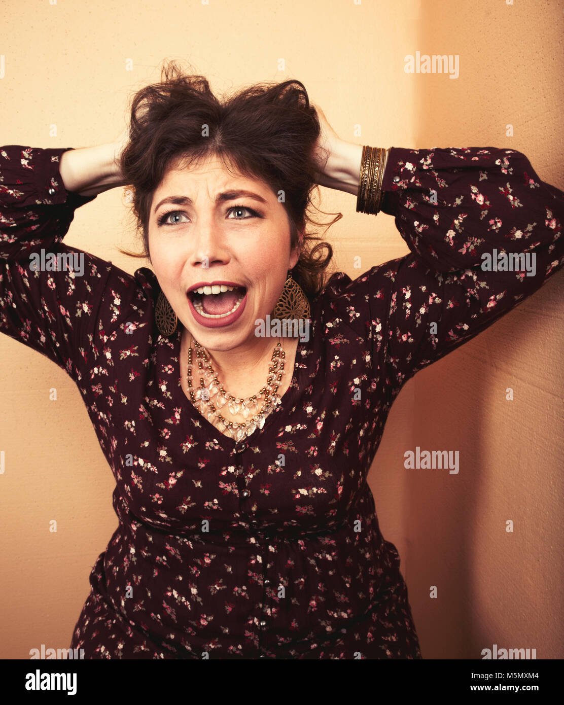 Woman pulling her hair and screaming. - Stock Image