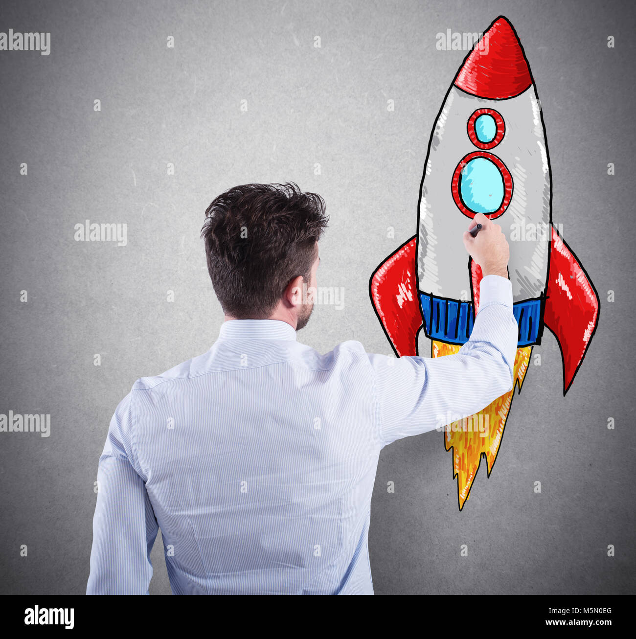 Businessman drawing a rocket. Concept of business improvement and enterprise startup - Stock Image