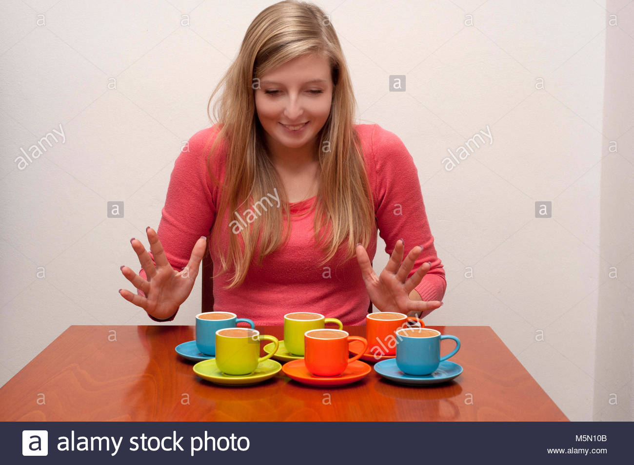 young woman sitting at table with colorful espresso coffee cups - Stock Image
