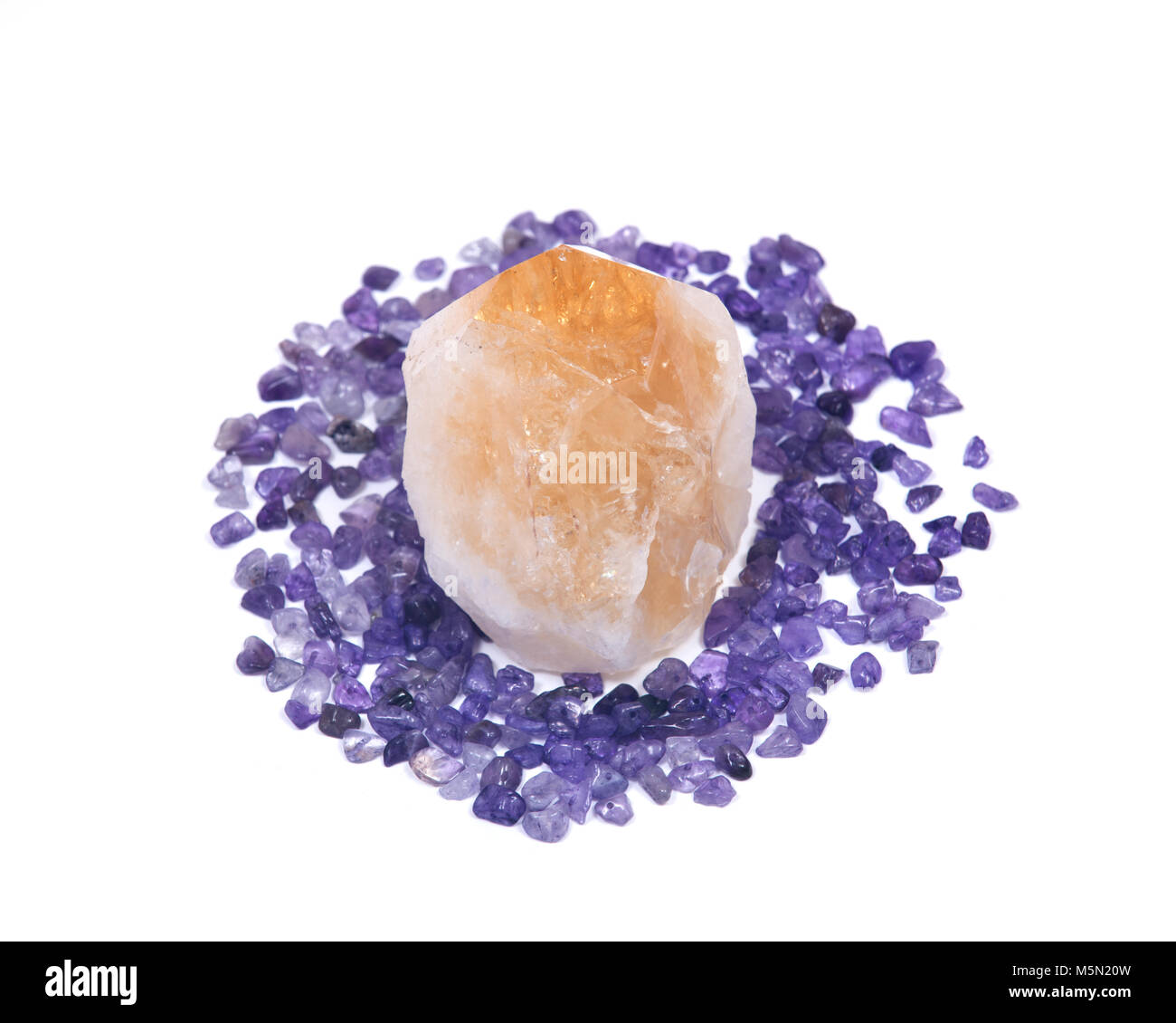 Natural citrine point surrounded by amethyst small tumbled chips isolated on white background - Stock Image