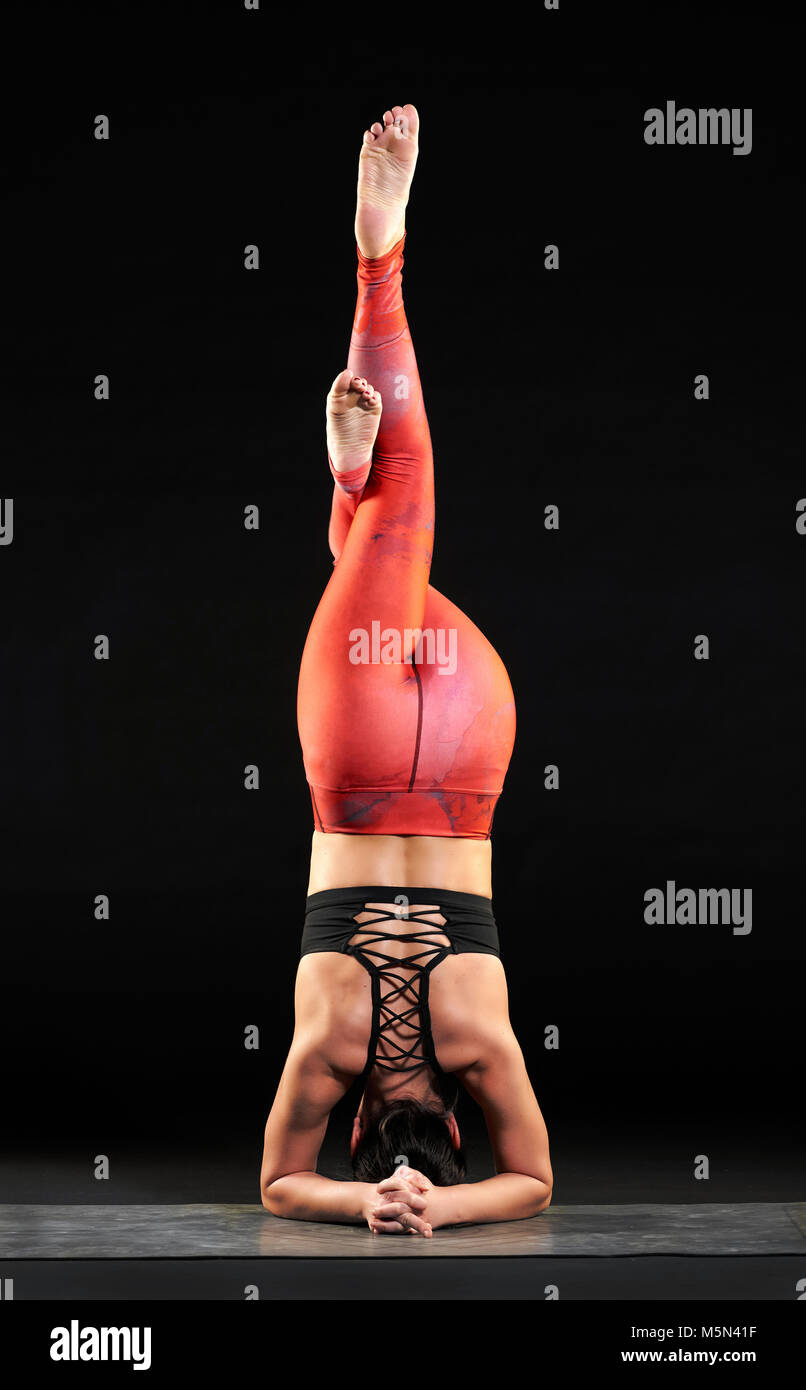 Woman demonstrating a headstand with eagle legs pose balancing on her forearms and head with body raised with legs - Stock Image