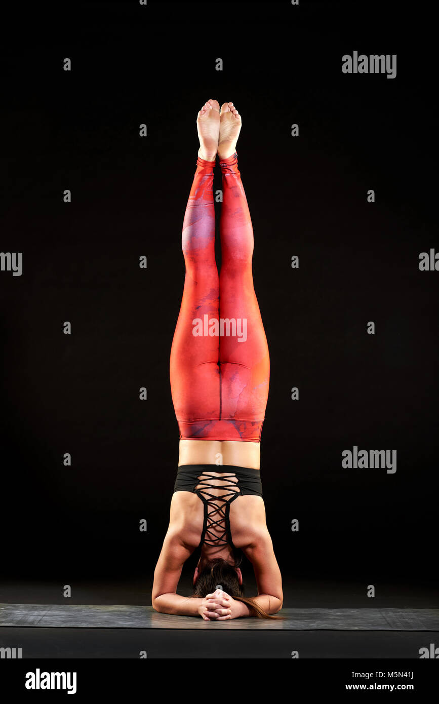 Fit Toned Young Woman Doing Headstand During A Yoga Workout Balancing On Her Head And Forearms With Body Raised Extended Over Black Background