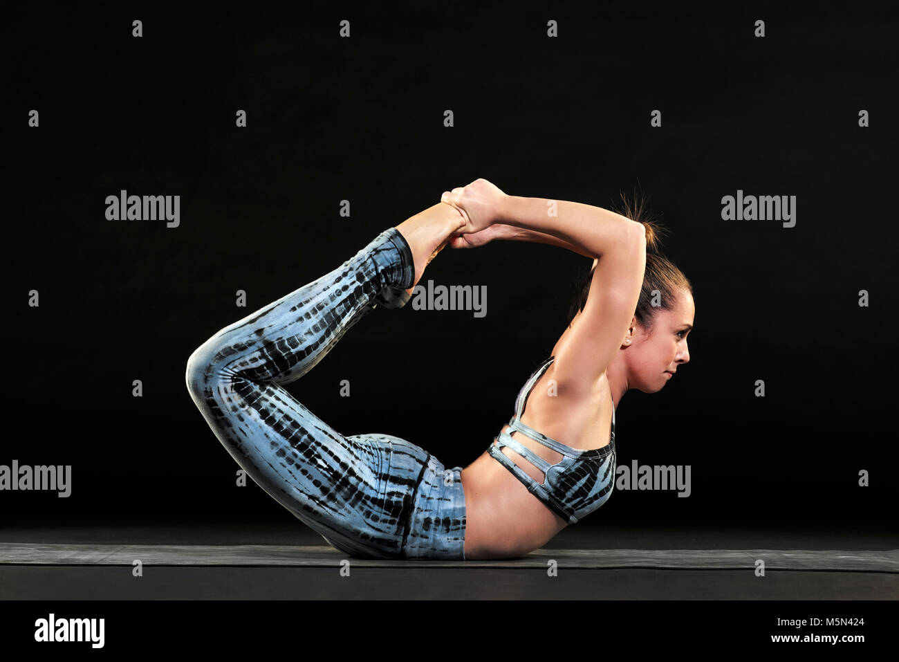 Athletic woman demonstrating the bow pose in yoga in a close up side view over a black background lying on her abdomen - Stock Image