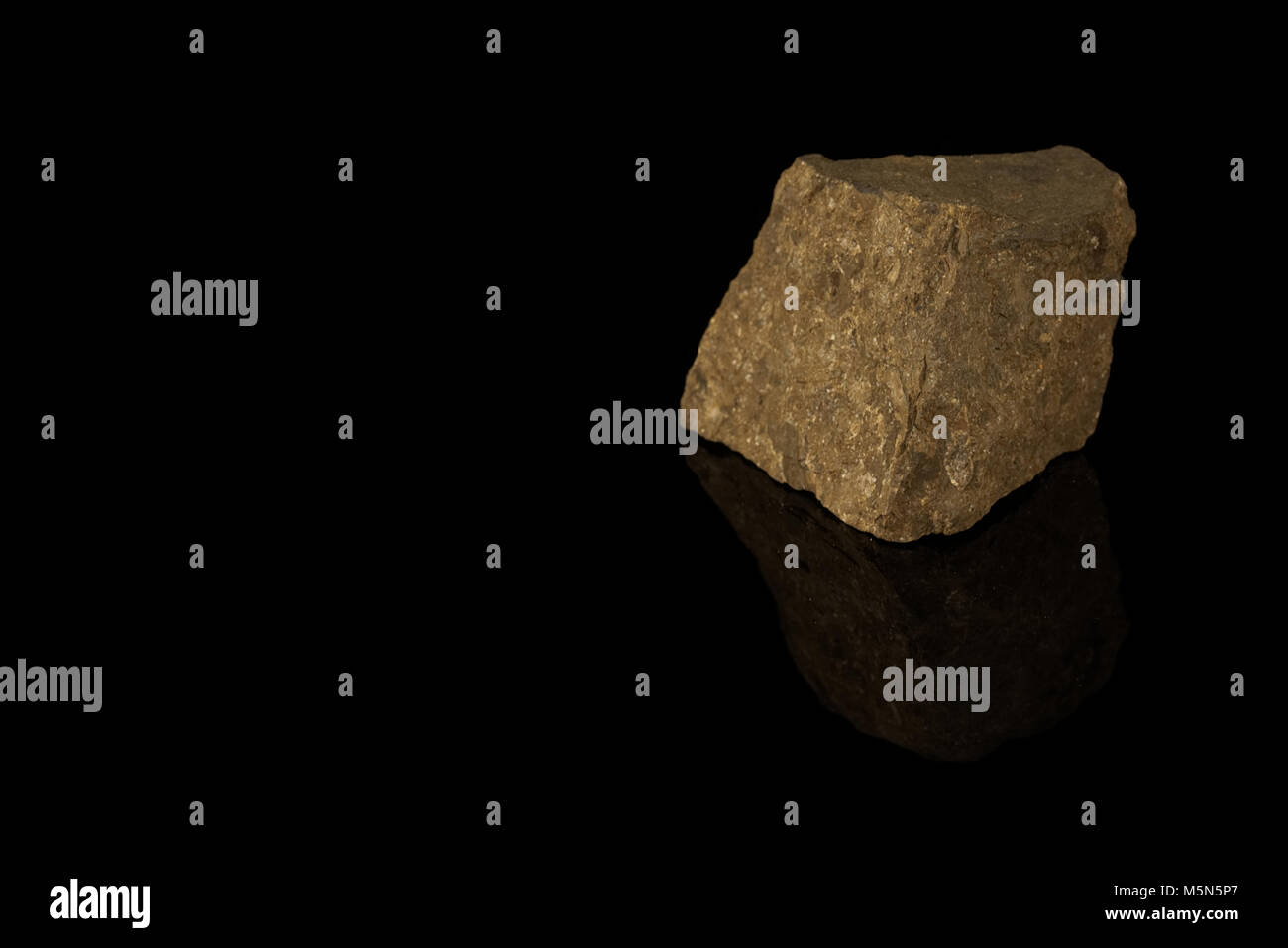 Manganese ore mineral isolated on a black background. Pyrolusite. Rocks and minerals - Stock Image
