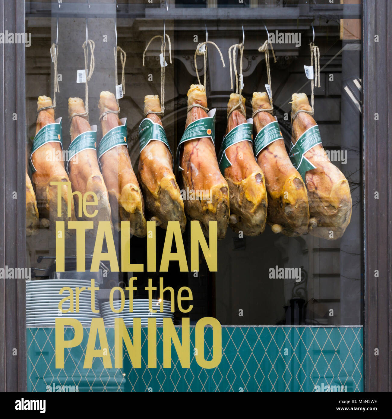 Parma hams hanging in the window of Panino Giusto in Royal Exchange Buildings in the City of London. - Stock Image