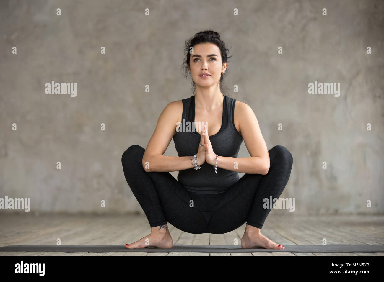 Young sporty woman practicing yoga, doing Garland exercise, Malasana pose, working out, wearing sportswear, black - Stock Image