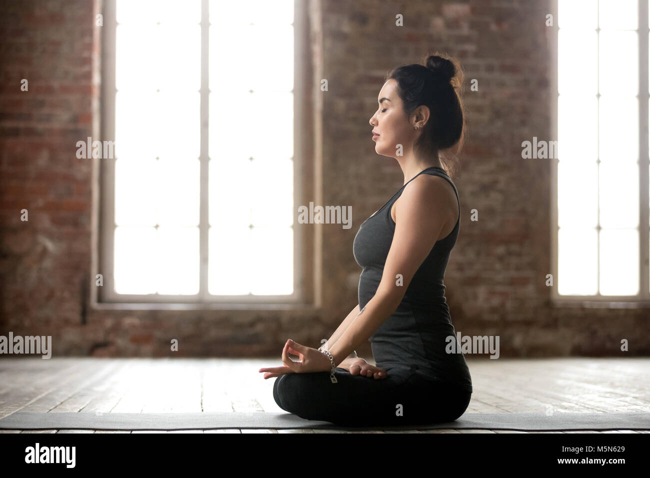 Young sporty woman practicing yoga, doing Padmasana exercise, Lotus pose, working out, wearing sportswear, black Stock Photo