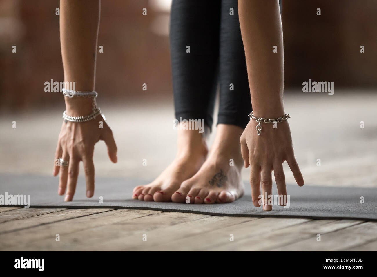 Young sporty woman practicing yoga, doing Head to knees pose, Uttanasana exercise, working out, wearing wrist bracelets, - Stock Image