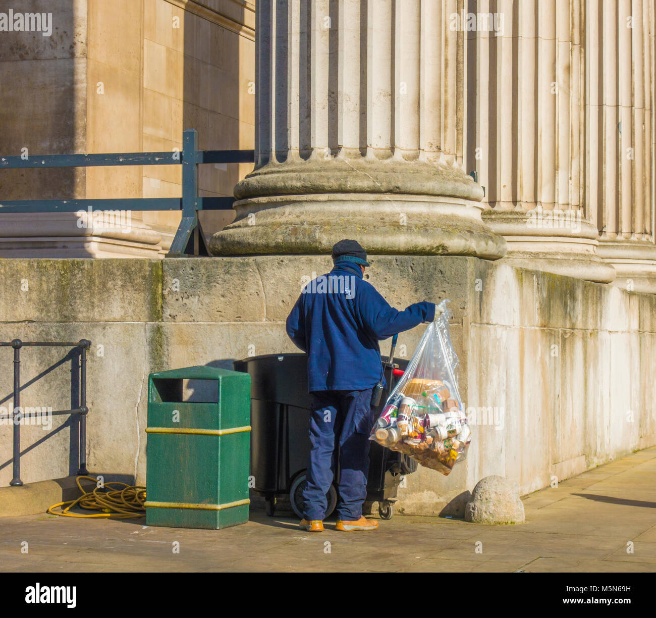 London worker outside The British Museum, lifting a full bin bag of mainly disposable cups, to place into a wheeled - Stock Image