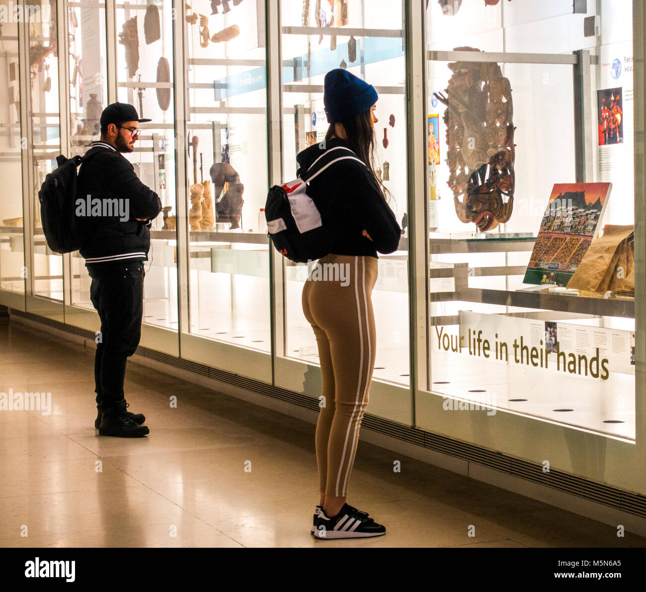 Young man and woman viewing historic artefacts through glass at The British Museum (dedicated to human history, - Stock Image