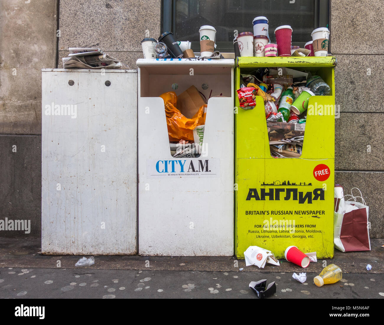 Free newspaper stands, turned into overflowing rubbish bins, with litter, consisting of mainly drinks containers, - Stock Image