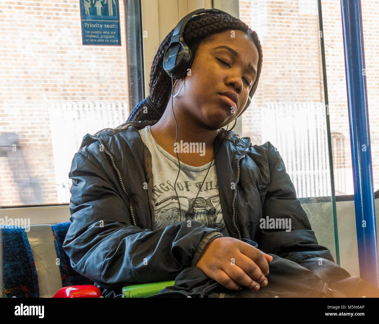 Young black woman passenger, dozing on a London Underground tube train while listening to music through headphones. - Stock Image