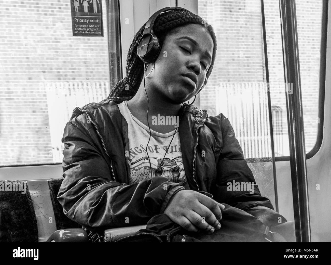 Black and white / monochrome. Young black woman passenger dozing on London Underground tube train, listening to - Stock Image