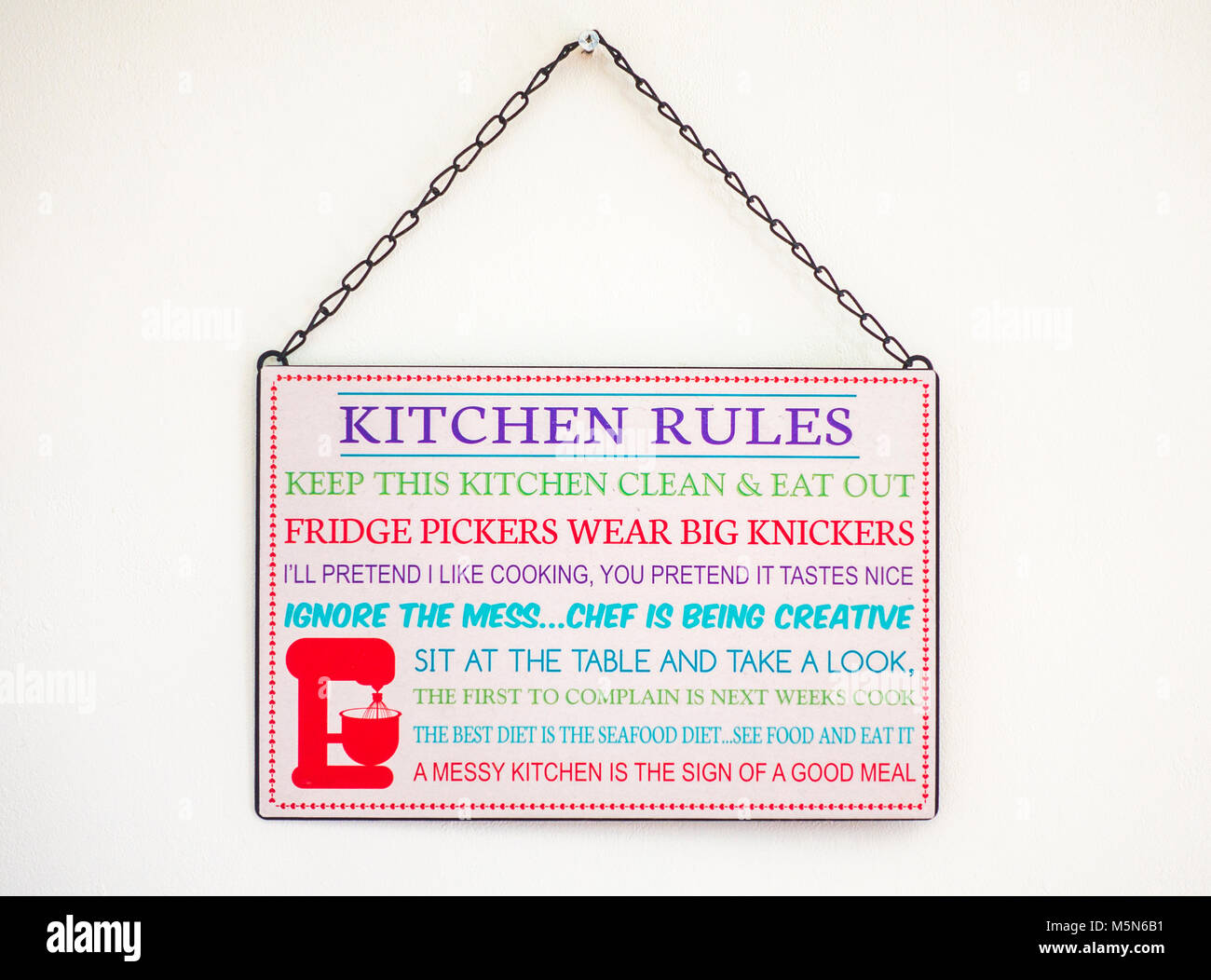 List of amusing kitchen rules, printed on an oblong sign, hanging by a chain on an interior home wall. England, - Stock Image