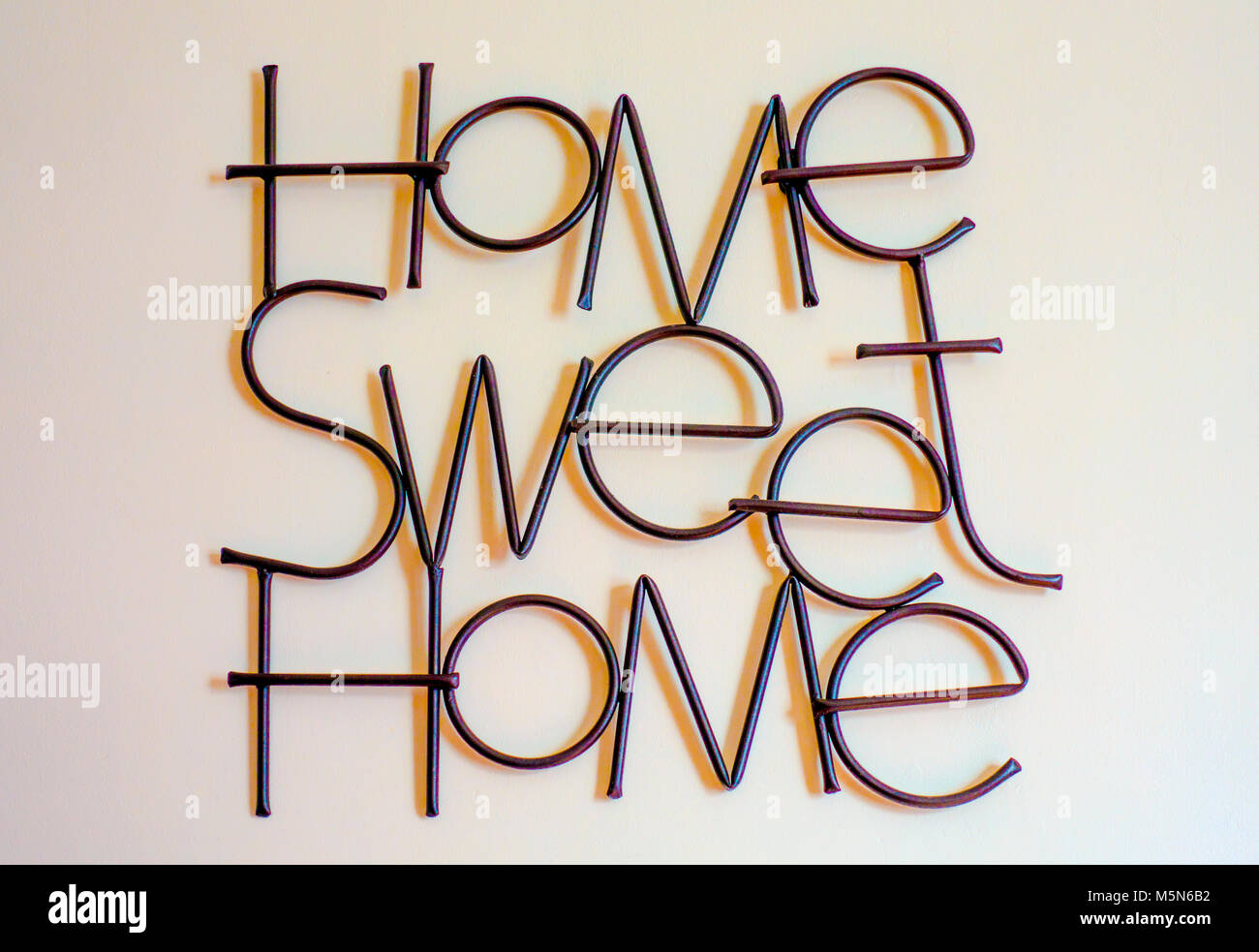 """The familiar motto """"Home Sweet Home"""", formed from metal lettering and affixed to an interior home wall. England, - Stock Image"""