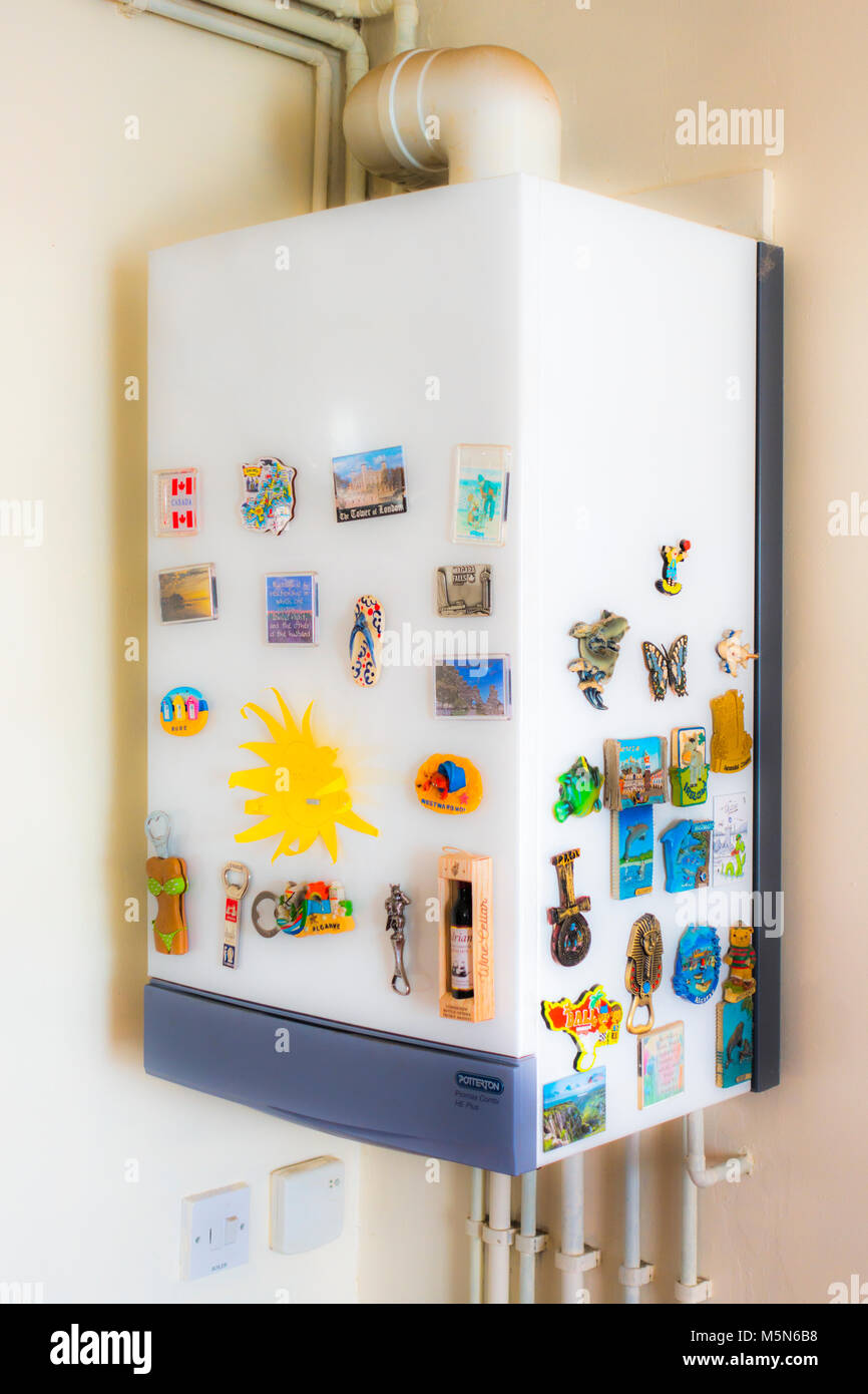A domestic home gas boiler, for central heating and hot water, wall hung in a room corner, covered in magnetic souvenirs - Stock Image
