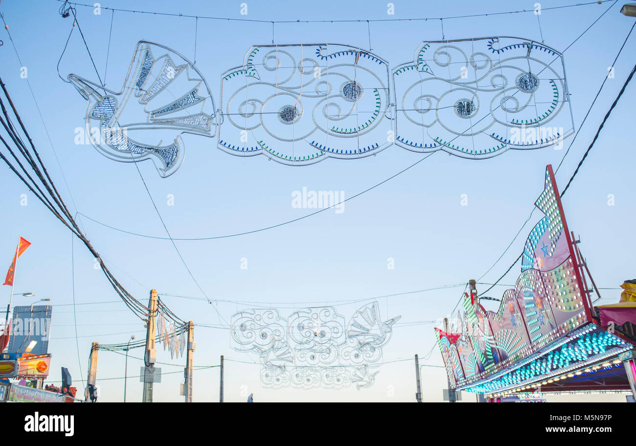 Fairground sky full of hanging decorations, bulbs, electrical wires and poles. Daylight shot - Stock Image