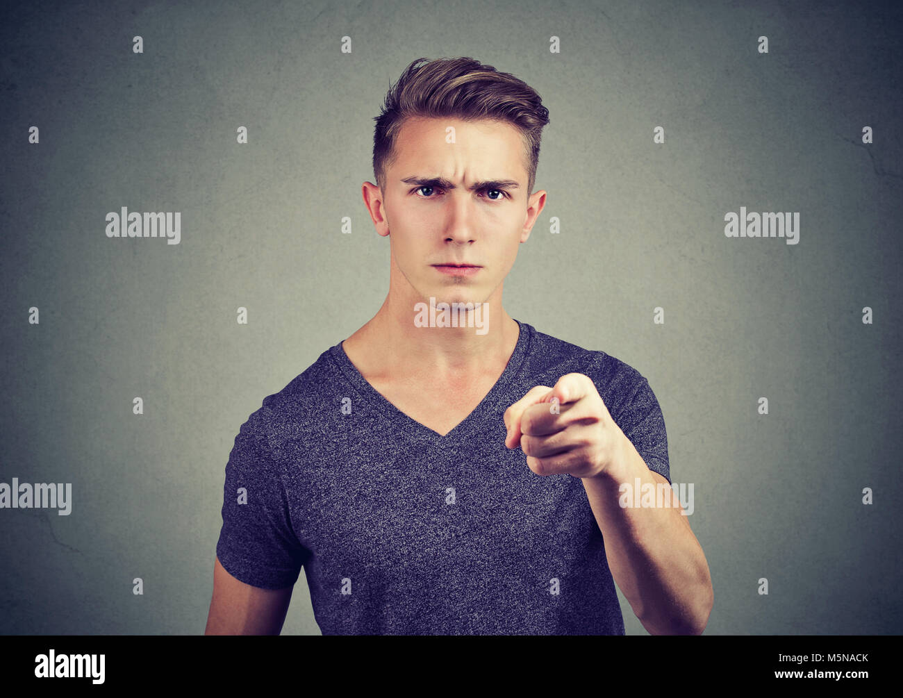 Young casual man pointing at camera with feelings of anger and accusation. - Stock Image