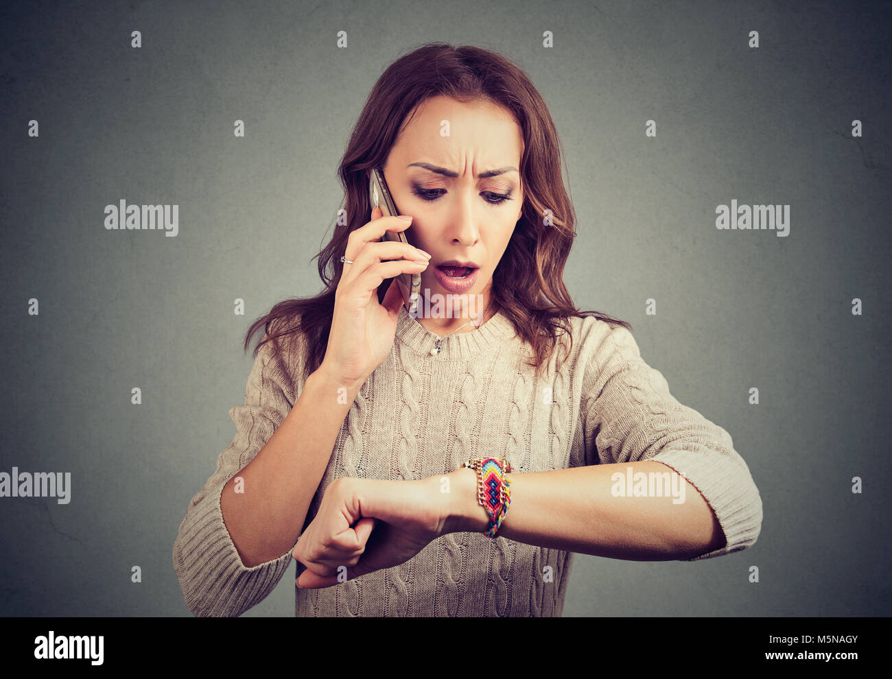 Young woman talking on smartphone and looking at wristwatch being late and stressful. - Stock Image