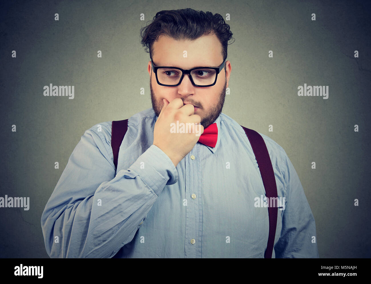 Portrait of a preoccupied anxious young man looking down - Stock Image