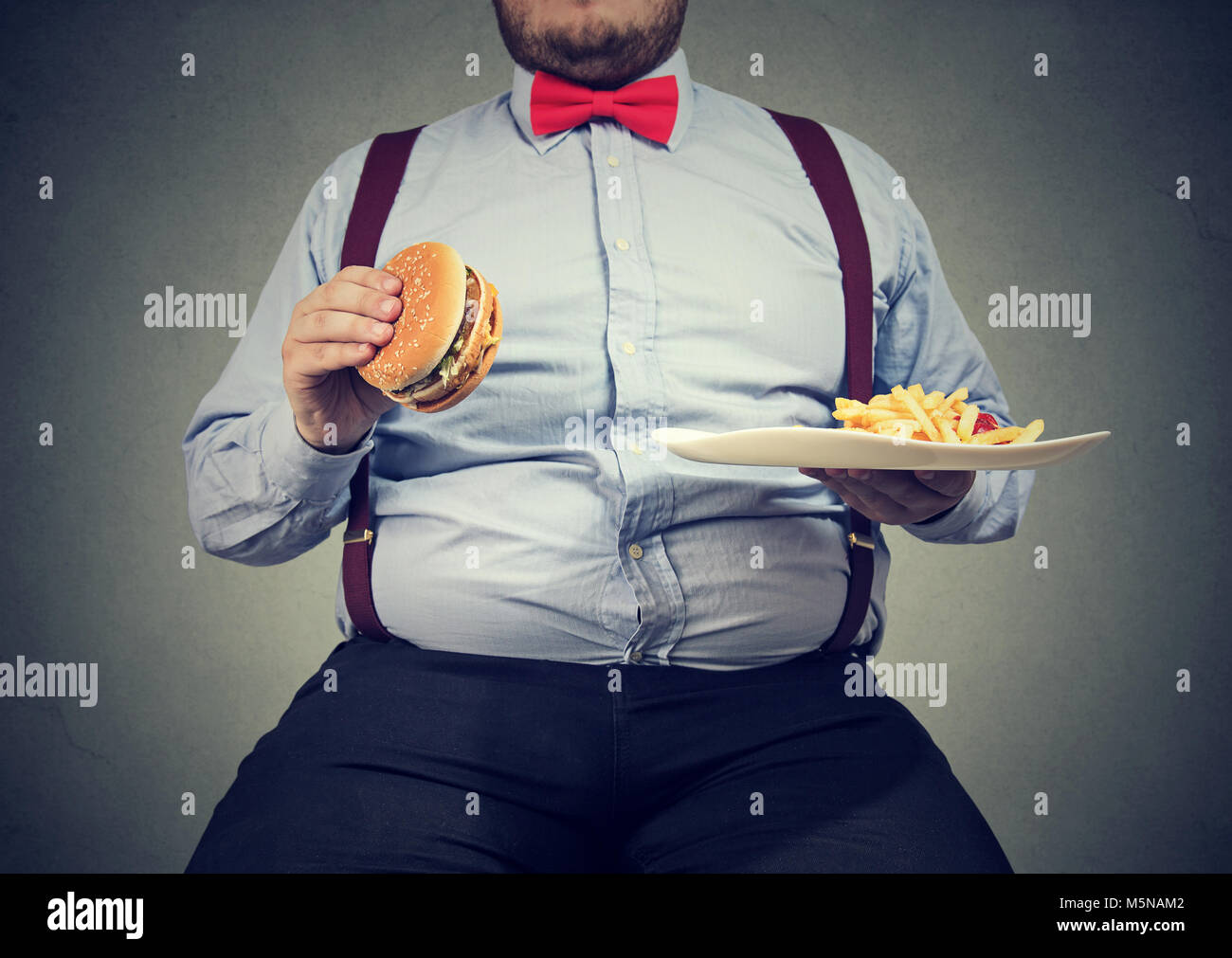 Crop shot of big man in formal clothes sitting and consuming plate with fast food on gray. - Stock Image