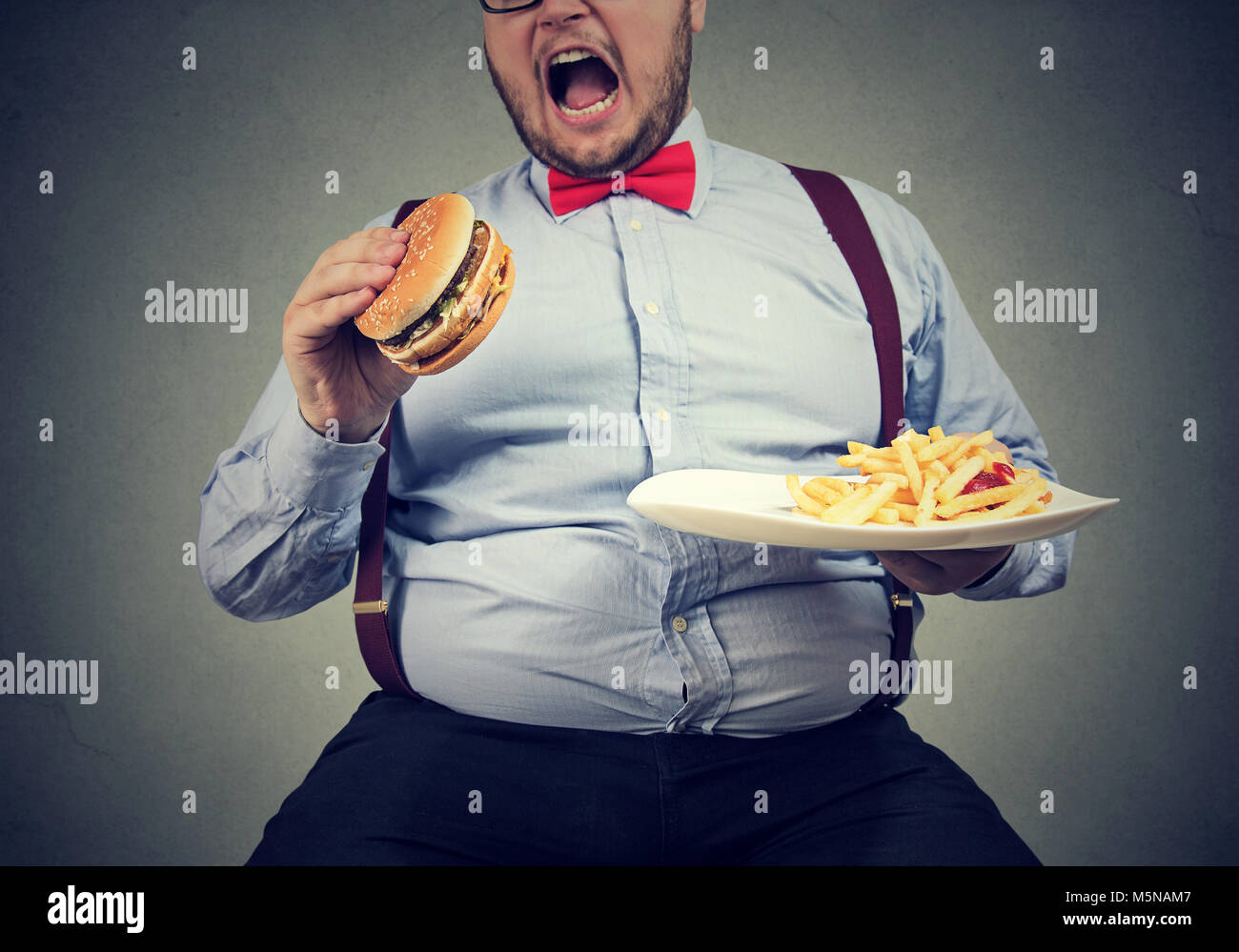 big man in formal clothes sitting and consuming plate with fast food on gray. - Stock Image