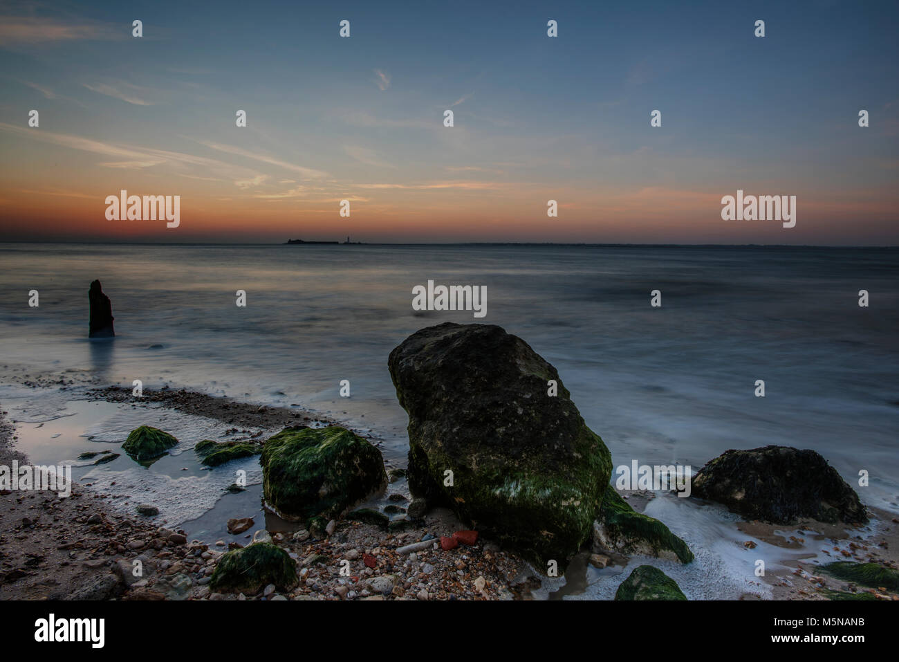 sunset or sun down over the beach on the coast of the isle of wight. atmospheric seascape or landscape at dusk with - Stock Image