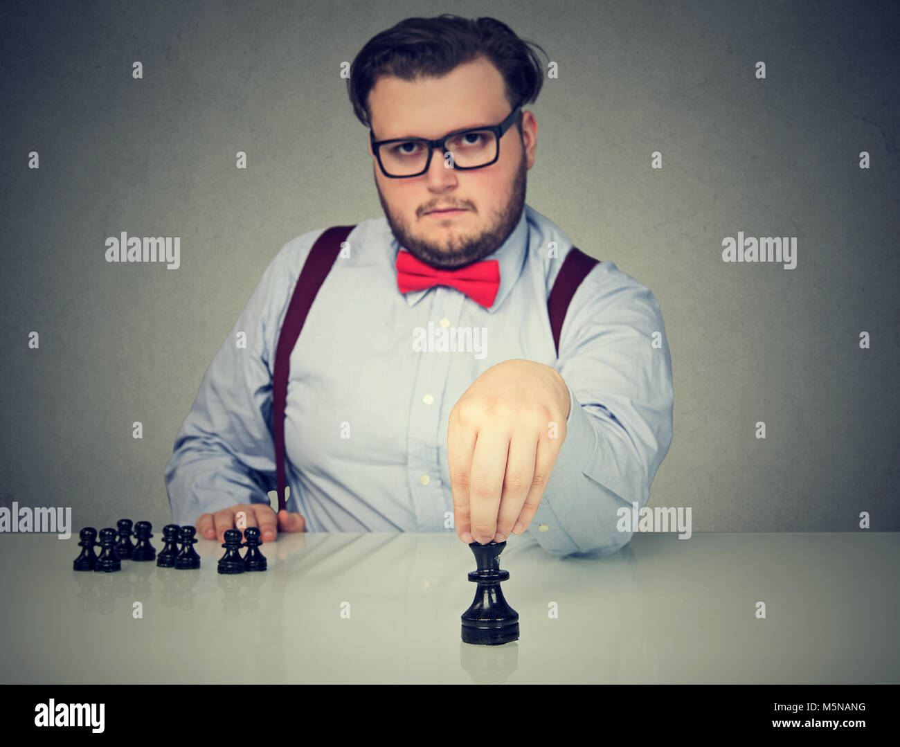 young serious business man playing chess game - Stock Image