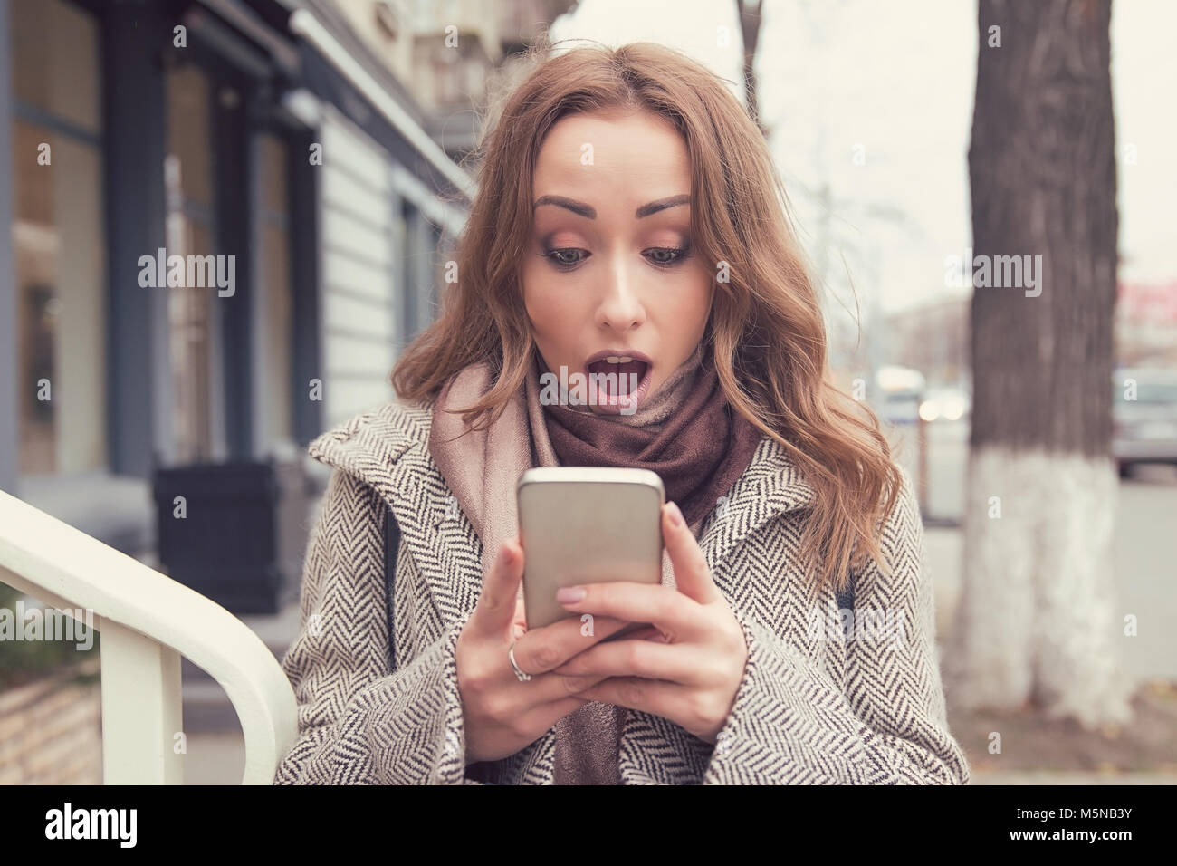 SMS. Funny shocked anxious girl looking at phone seeing bad news photos message with surprised face expression on - Stock Image