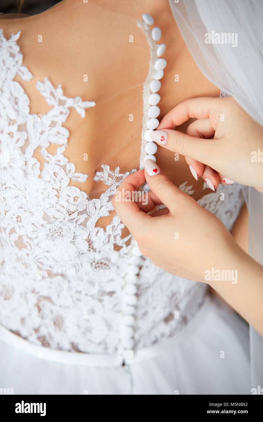 Bride's beautiful back in fantastic white wedding dress and hands zipping it - Stock Image