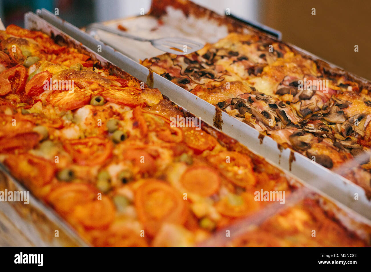 A delicious baked traditional pizza with cheese, tomatoes, mushrooms and olives is sold in the bakery. - Stock Image